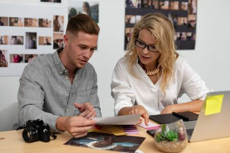 Front view of Caucasian male and female graphic designers discussing over photo at desk in office. This is a casual creative start-up business office for a diverse team