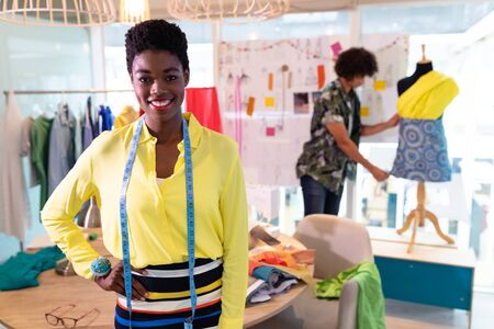 Front view of pretty young African american female fashion designer standing with hand on hip in design studio. Mixed race man working in the background. This is a casual creative start-up business office for a diverse team