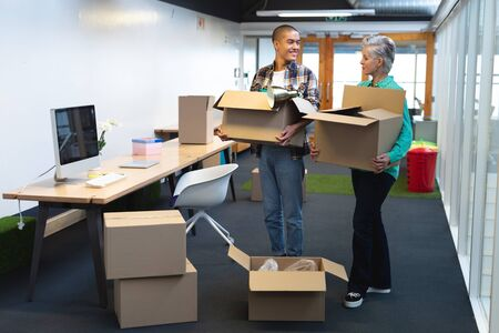 Side view of happy diverse male and female executives carrying cardboard boxes in office. This is a casual creative start-up business office for a diverse team