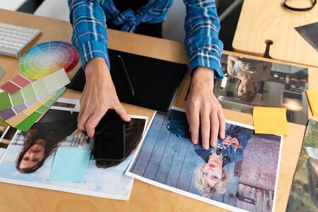 Nahaufnahme der kaukasischen Grafikdesignerin mit Handy am Schreibtisch im Büro. Dies ist ein lässiges, kreatives Start-up-Geschäftsbüro für ein vielfältiges Team