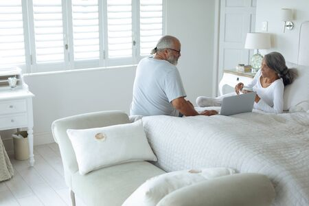 Side view of senior diverse couple sitting on bed inside a room. Authentic Senior Retired Life Concept