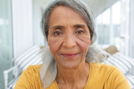 Front view of African American Woman inside a room smiling. Authentic Senior Retired Life Concept