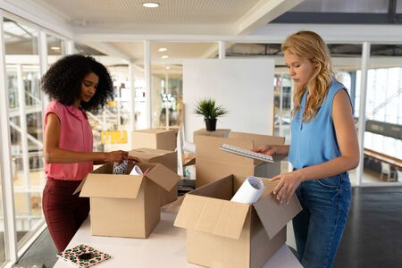 Side view of young diverse female executives unpacking cardboard boxes in office. This is a casual creative start-up business office for a diverse team