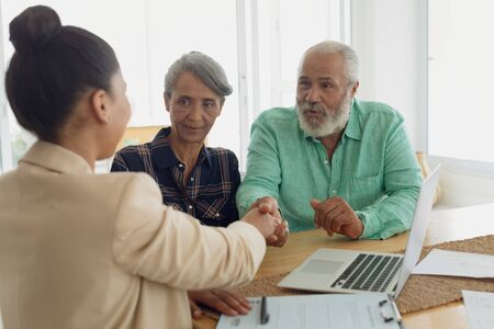 Side view of African-American man shaking hands with financial adviser while sitting beside wife indoor. Authentic Senior Retired Life Concept