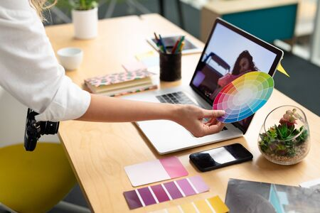 Mid section close-up of Caucasian female graphic designer holding a color swatch at desk in office. This is a casual creative start-up business office for a diverse team 免版税图像