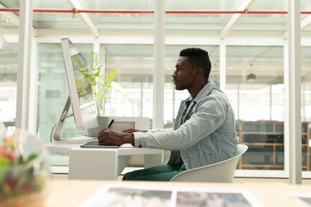 Side view of African american male graphic designer using graphic tablet at desk in office. This is a casual creative start-up business office for a diverse team