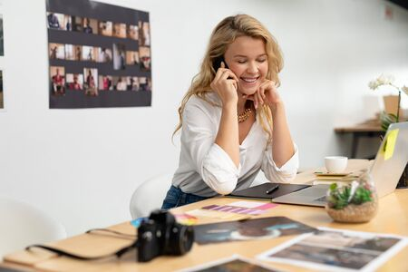 Front view of Caucasian female graphic designer talking on mobile phone at desk in office. This is a casual creative start-up business office for a diverse team Banco de Imagens