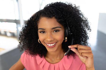 Retrato de mujer afroamericana ejecutiva de servicio al cliente hablando por auriculares en el escritorio en la oficina. Esta es una oficina de negocios de puesta en marcha creativa informal para un equipo diverso