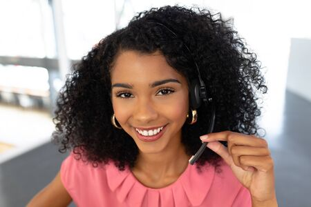 Portrait of African american female customer service executive talking on headset at desk in office. This is a casual creative start-up business office for a diverse team