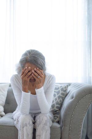 Vista frontal de la mujer de raza mixta senior preocupada sentada en el sofá en casa. Auténtico concepto de vida jubilado senior Foto de archivo