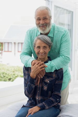 Front view close up of African-American  couple smiling inside a room. Authentic Senior Retired Life Concept