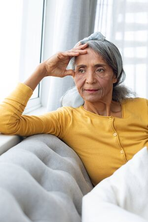 Front view of African American Woman inside a room thinking. Authentic Senior Retired Life Concept