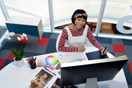 Front view of young pretty Asian female graphic designer using graphic tablet at desk in office. This is a casual creative start-up business office for a diverse team