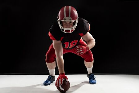 Young American football player in helmet taking position against black background. Strong American Football Player concept for Championship Football Tournament 스톡 콘텐츠