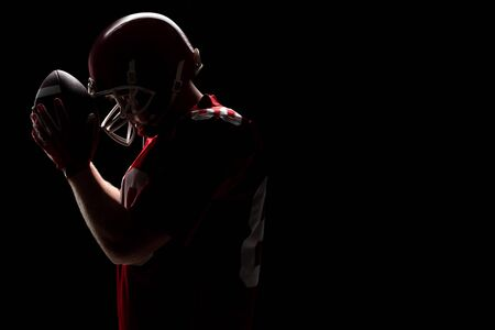 Side view of American football player standing with rugby helmet and ball. Strong American Football Player concept for Championship Football Tournament Stock Photo