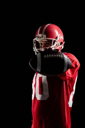 American football player standing with rugby ball and helmat against black background. Strong American Football Player concept for Championship Football Tournament 스톡 콘텐츠