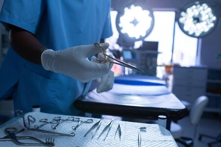 Mid section close-up of African-american surgeon holding surgical scissor in operating room. Shot in real medical hospital with doctors nurses and surgeons in authentic setting