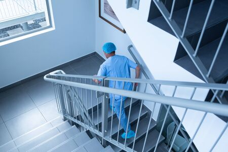 High angle view of Caucasian male surgeon running upstairs in hospital. Shot in real medical hospital with doctors nurses and surgeons in authentic setting