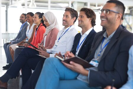 Side view of diverse happy audience listening to speaker in a business seminar. International diverse corporate business partnership concept