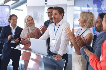 Front view of mature Caucasian businessman standing with diverse colleagues and speaks in a business seminar. International diverse corporate business partnership concept