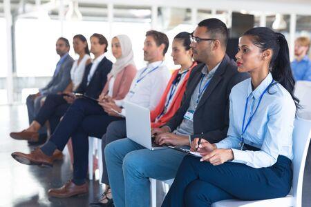 Zijaanzicht van divers publiek dat luistert naar spreker in een zakelijk seminar. Internationaal divers zakelijk partnerschapsconcept