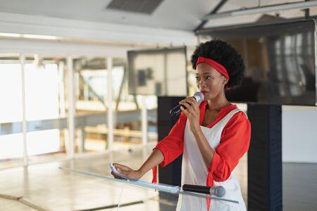 Widok z przodu pięknej wykonawczej kobiety rasy mieszanej ćwiczącej przemówienie w sali konferencyjnej w biurze