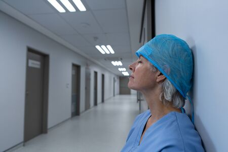 Side view of upset Caucasian female surgeon eyes closed sitting in the corridor at hospital. Shot in real medical hospital with doctors nurses and surgeons in authentic setting