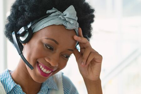 Front view of beautiful happy mixed-race female customer service executive talking on headset in office. New start-up business with entrepreneur working hard Banco de Imagens