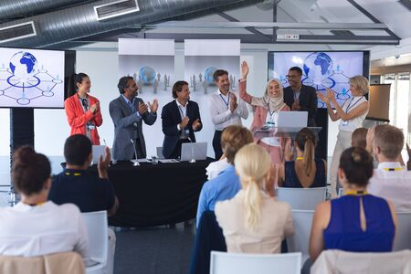 Front view of beautiful young mixed-race businesswoman in hijab standing with diverse colleagues and speaks in a business seminar. International diverse corporate business partnership concept