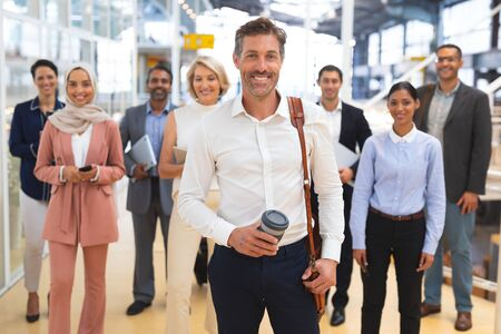 Front view of Happy diverse  business people looking at camera while standing in a modern office. International diverse corporate business partnership concept
