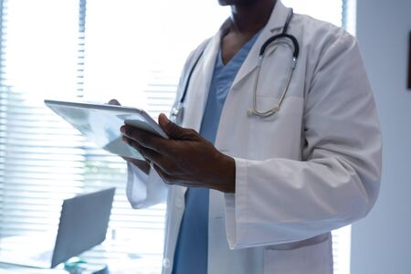Mid section of African-american male doctor using digital tablet in the hospital. Shot in real medical hospital with doctors nurses and surgeons in authentic setting