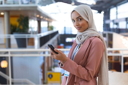 Portrait of beautiful young mixed race businesswoman in hijab looking at camera while using mobile phone in a modern office. International diverse corporate business partnership concept