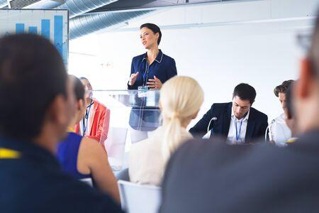 Vista frontal del orador mujer caucásica habla en un seminario de negocios. Concepto de asociación de negocios corporativos diversos internacionales