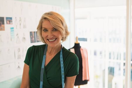 Portrait of happy mature Caucasian female fashion designer standing in design studio. Modern casual creative business concept