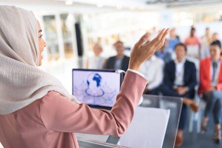 Primer plano de una hermosa oradora de raza mixta en hijab dando un discurso en un seminario de negocios. Concepto de asociación de negocios corporativos diversos internacionales