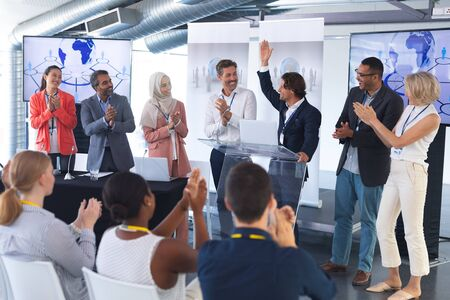 Front view of young handsome Caucasian businessman standing with diverse colleagues and speaks in a business seminar. International diverse corporate business partnership concept