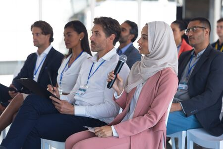 Side view of mixed-race businesswoman in hijab asking question during seminar. International diverse corporate business partnership concept Foto de archivo