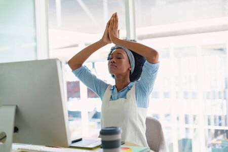 Front view of beautiful young mixed-race female graphic designer performing yoga at desk in office. New start-up business with entrepreneur working hard
