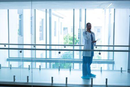 Seitenansicht des weiblichen Chirurgen gemischter Rassen, der auf dem Flur im Krankenhaus telefoniert. Gedreht in einem echten medizinischen Krankenhaus mit Ärzten, Krankenschwestern und Chirurgen in authentischer Umgebung Standard-Bild