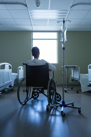 Rear view of disabled Mixed race female patient looking through window while sitting in wheelchair in hospital. Shot in real medical hospital with doctors nurses and surgeons in authentic setting