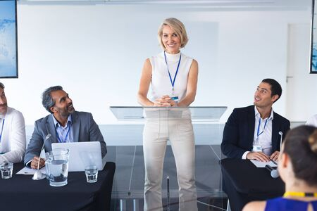 Front view of caucasian female speaker speaks in a business seminar. International diverse corporate business partnership concept