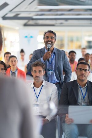 Front view of caucasian businessman asking question during seminar. International diverse corporate business partnership concept Foto de archivo