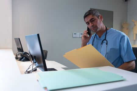 Side view of Caucasian male surgeon talking on mobile phone while looking at medical report at desk in hospital. Shot in real medical hospital with doctors nurses and surgeons in authentic setting Stock Photo