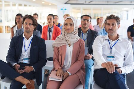 Front view of diverse audience listening to speaker in a business seminar. International diverse corporate business partnership concept Banco de Imagens