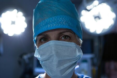 Portrait close-up of Caucasian female surgeon standing in operation theater while looking at camera at hospital. Shot in real medical hospital with doctors nurses and surgeons in authentic setting