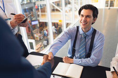 Vista frontal de empresarios caucásicos dándose la mano mientras se registran en la mesa de registro de la conferencia. Concepto de asociación de negocios corporativos diversos internacionales Foto de archivo