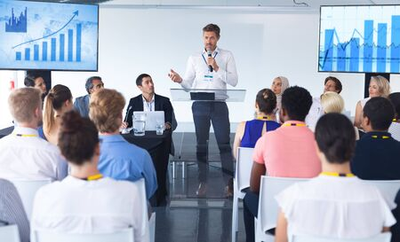 Front view of Caucasian male speaker speaks in a business seminar at conference meeting. International diverse corporate business partnership concept