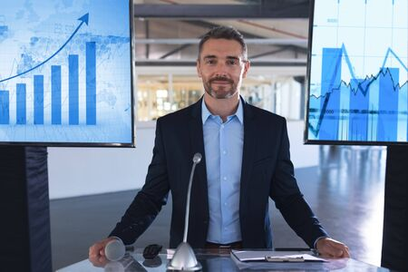 Front view of caucasian Male speaker looking at camera while standing at podium in business seminar. International diverse corporate business partnership concept