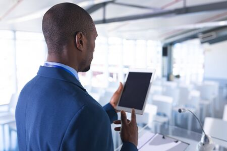 Rear view of African-american Male speaker practicing his speech on digital tablet in business seminar at conference room. International diverse corporate business partnership concept
