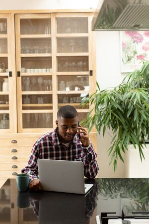 Front view of African-american man talking on mobile phone while using laptop on worktop in kitchen at comfortable home. Authentic home lifestyle setting with young African American male